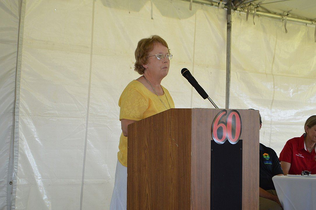 Woman in Yellow Shirt Speaking at Podium